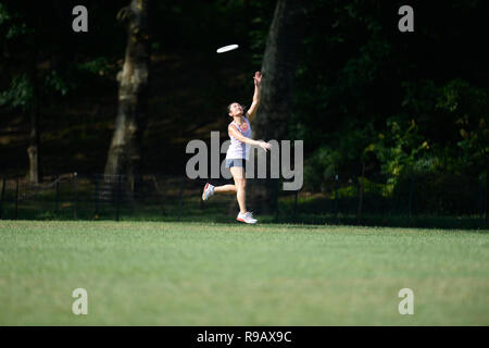 Girl playing frisbee in Central Park in New York City - Stock Image