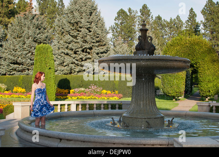 Pretty young woman plays in the Davenport Fountain, Duncan Garden, Manito Park, Spokane, Washington State, USA. - Stock Image