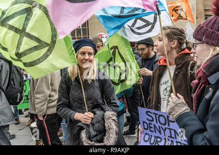 London, UK. 21st December 2018. Climate campaigners from Extinction Rebellion protest at the BBC calling it to stop ignoring the climate emergency & mass extinctions taking place and promoting destructive high-carbon living through programmes such as Top Gear and those on fashion, travel, makeovers etc. The protest, organised by the Climate Media Coalition (CMC) and its director Donnachadh McCarthy brought mannequins wrapped in white cloth to the BBC representing the bodies of a Greek village killed by fire. Peter Marshall/Alamy Live News - Stock Image