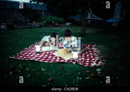 Children read books by lantern light on blanket in garden in evening. - Stock Image