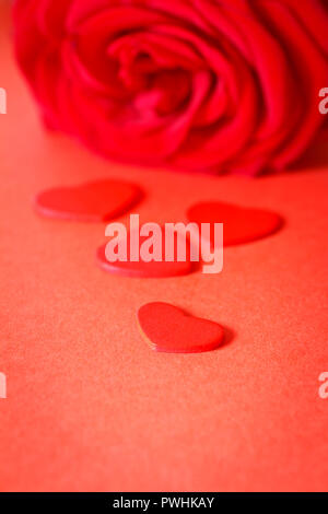 Red rose flower with little hearts on a red background. Romantic texture for a Valentine's or Wedding day greetings card with text space. - Stock Image