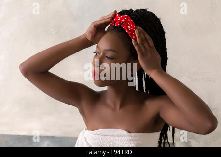 Young woman with afro hairstyle preparing to take a bath in a vintage white bathroom - Stock Image