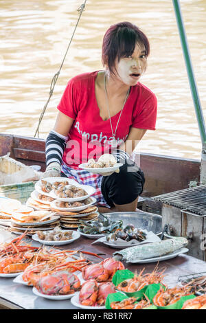 Amphawa, Thailand - 7th October 2018: Grilling and selling seafood from a boat, A floating market is held every weekend. - Stock Image