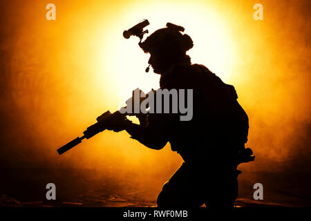 Black silhouette of soldier in the burning fire during a battle operation. - Stock Image