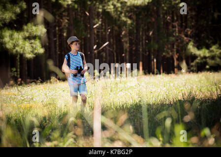 Boy walking through meadow with binoculars - Stock Image