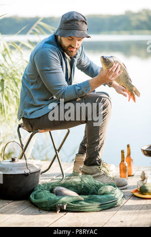 Happy fisherman holding caught fish ready to cook sitting during the fishing process near the lake - Stock Image
