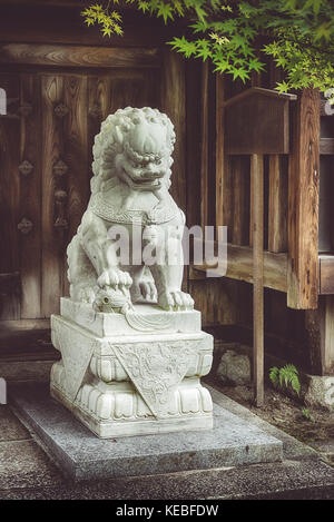A Komainu guards a shinto shrine in Kyoto - Stock Image