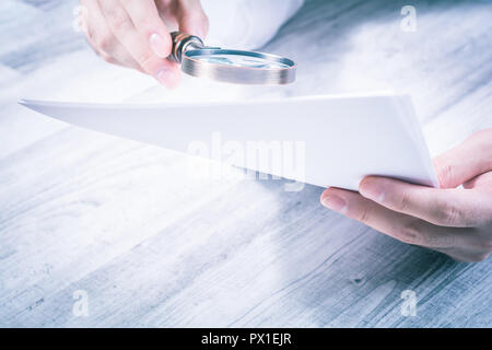 Businessman Reading His Documents With A Magnifying Glass - Stock Image