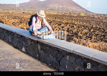 Young lonely woman wild traveler sitting and looking at the map for the road trip plane with desert and mountains in background - enjoying different v - Stock Image