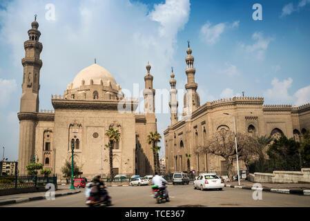 Traffic driving past The Mosque-Madrassa of Sultan Hassan, Mokattam Hill, Cairo, Egypt - Stock Image