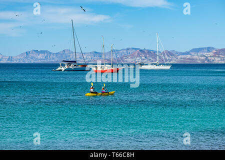 A couple paddle a yellow kayak with sailboats and mountains in the background as birds fly overhead off shore of Isla San Francisco, Baja California S - Stock Image
