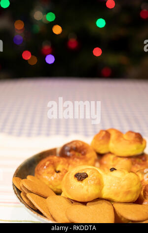 A plate of traditional Swedish saffron bread and ginger snaps with blurred colored Christmas tree lights in the background. - Stock Image