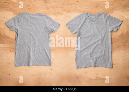 Front and back of grey melange empty T-shirt on wooden background. Horizontal view. - Stock Image