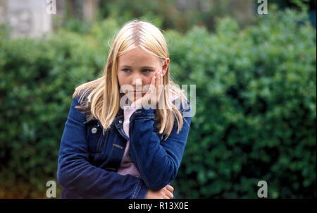 unhappy teenage girl sitting alone outside - Stock Image