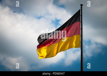 German flag fluttering in the wind with the blue sky with white clouds in a background - Stock Image