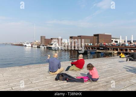 People sitting on by the water; Kvæsthusmolen, Copenhagen Harbour, Denmark - Stock Image