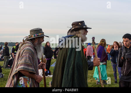 Stonehenge, Amesbury, UK, 21st June 2018,   2 men with staffs walking towards the stones at the summer solstice  Credit: Estelle Bowden/Alamy Live News. - Stock Image