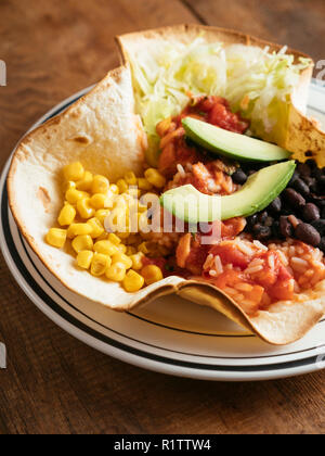 Mexican taco bowl with lettuce, corn, Mexican spicy, tomato rice, black beans, salsa and avocado on a flour tortilla. - Stock Image