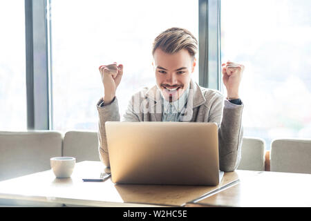 Portrait of handsome amazed satisfied positive bearded young freelancer in grey blazer are sitting in cafe, watching online football match with toothy - Stock Image