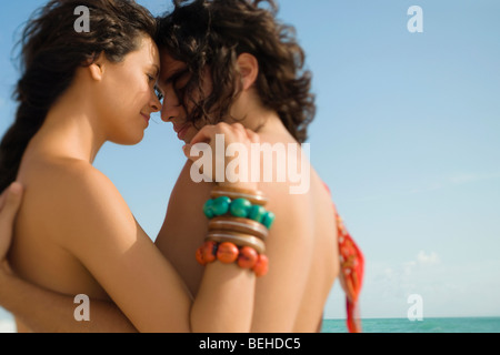 Side profile of a young couple romancing on the beach - Stock Image