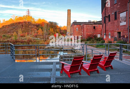 Sitting on the red Muskoka chairs and admiring autumn view from old ruins of Don Valley Evergreen Brickworks - Stock Image