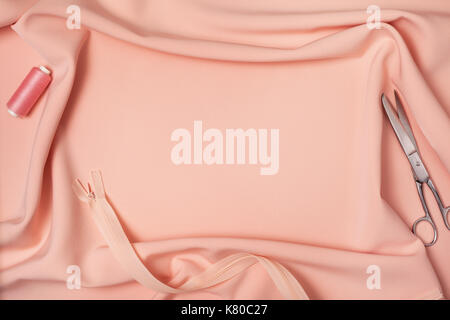 background of peach fabric drapery, scissors, thread, zipper. view from above - Stock Image