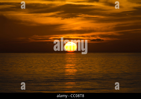 The sun first touched the horizon, create a beautiful golden glow on the water and the light, wispy clouds above. - Stock Image