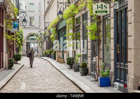 Woman walks the cobblestone road, Cour Damoye, near Bastille, 11th Arrondissement, Paris, France - Stock Image