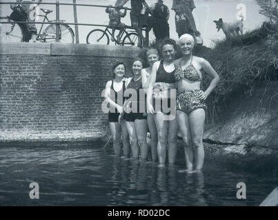 c 1940, historical, ladies in bathing costumes of the day standing in a shallow part of a river with on lookers standing on a bridge, England, UK. One of the brave ladies is wearing what looks like a lifebelt around her waist. - Stock Image