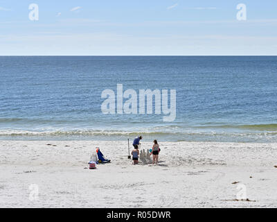 Family building a sand castle on the Florida beach at Deer Lake State Park, Florida USA. - Stock Image