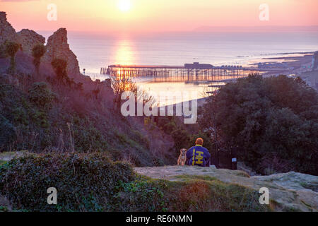 Hastings, UK. 20th January 2019. On a calm sunny evening a boy and his dog sit and watch the sunset from beside the Castle ruins, overlooking the pier and the sea to distant Beachy Head. - Stock Image