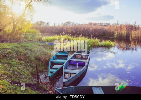 Two wooden fishing boats on a sunset background in autumn on the water - Stock Image