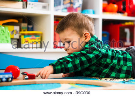 Poznan, Poland - April 6, 2018: Toddler boy laying on a floor and trying to reach toys in a child room. - Stock Image