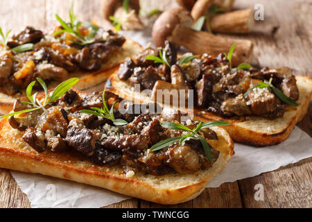 Toasts with fried porcini mushrooms, onions, thyme and parmesan cheese closeup on the table. horizontal - Stock Image