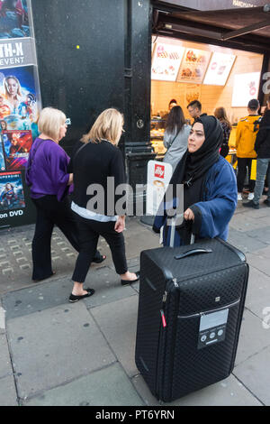 Muslim woman with very large wheeled suitcase on the street in london - Stock Image