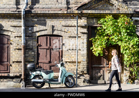 Woman walking past a scooter on the streets of the alternative neighborhood of Uzupis, Vilnius, Lithuania - Stock Image