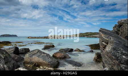 The turquoise blue waters of the Atlantic shoreline lapping between the rocks at Bostadh Beach, Isle of Lewis, Outer - Stock Image