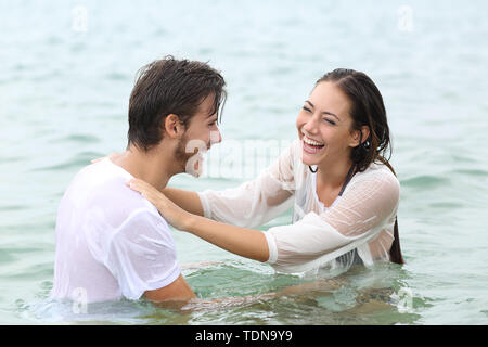Funny couple joking bathing on the beach on summer vacation - Stock Image