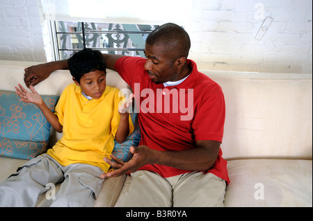 African American father and son having a difficult conversation - Stock Image