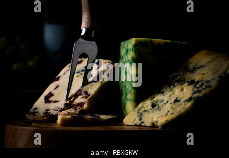 dark mood cheese board selection with Wensleydale, Stilton and Sage Derby against a dark background - Stock Image