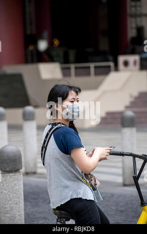 Female cyclist in Shanghai, China, wearing a face mask - Stock Image