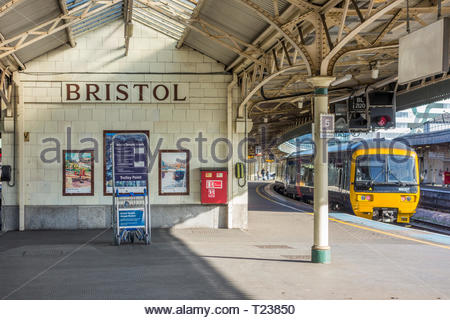 Bristol sign on glazed ceramic tiles and a train at the platform at Bristol Temple Meads Railway Station, England, UK - Stock Image