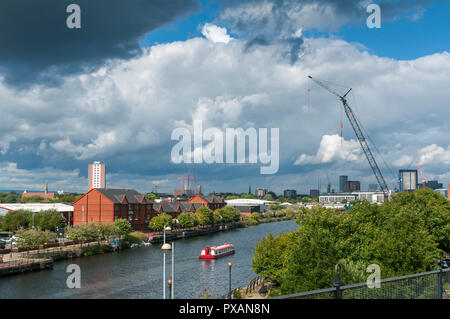 A tourist sightseeing boat on the river Irwell - Manchester Ship Canal from the Pomona Metrolink Tram stop. Manchester, England, UK - Stock Image
