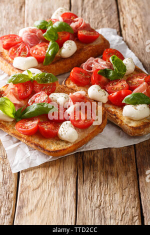 Italian sandwiches with mozzarella, tomatoes, prosciutto and basil close-up on the table. vertical - Stock Image