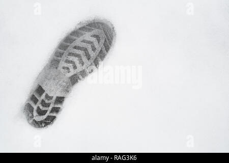 one left foot shoe print on snow, top view, copy space, cloudy, no sunshine - Stock Image