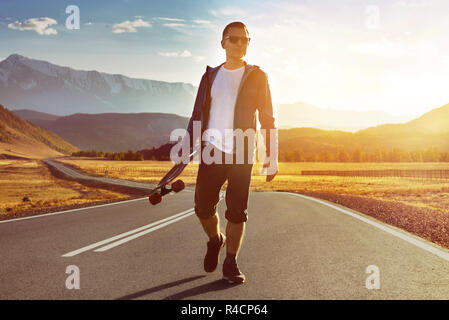 Happy man skater walks with longboard by sunset mountain road. Skating or longboarding concept - Stock Image