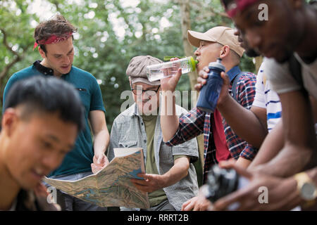 Mens group with map and water bottles hiking in woods - Stock Image