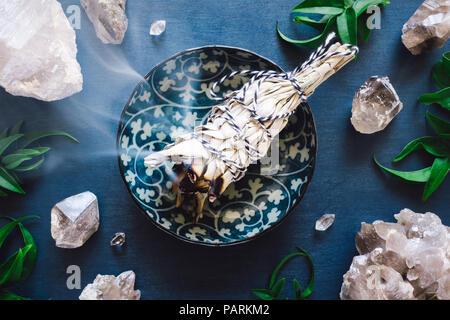 Burning Smudge with Quartz on Blue Table - Stock Image