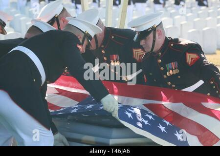 Marine Corps Body Bearers, Bravo Company, Marine Barracks Washington D.C., prepare to fold the National Flag during a full honors funeral for Lt. Gen. Leo Dulacki at Arlington National Cemetery, Arlington, Virginia, March 13, 2019. Dulacki enlisted in the Marine Corps in 1941 and received his commission as a second lieutenant on Sept. 2, 1941. During his 32 years of service, Dulacki fought in World War II, Korea and Vietnam; he retired in January 1974. His personal decorations included the Distinguished Service Medal with a gold star, Legion of Merit with a combat distinguishing device for val - Stock Image