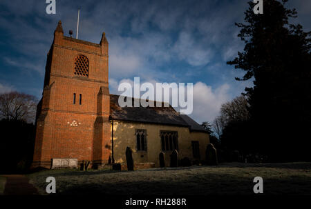 English village church with tower in early morning sunlight - Stock Image